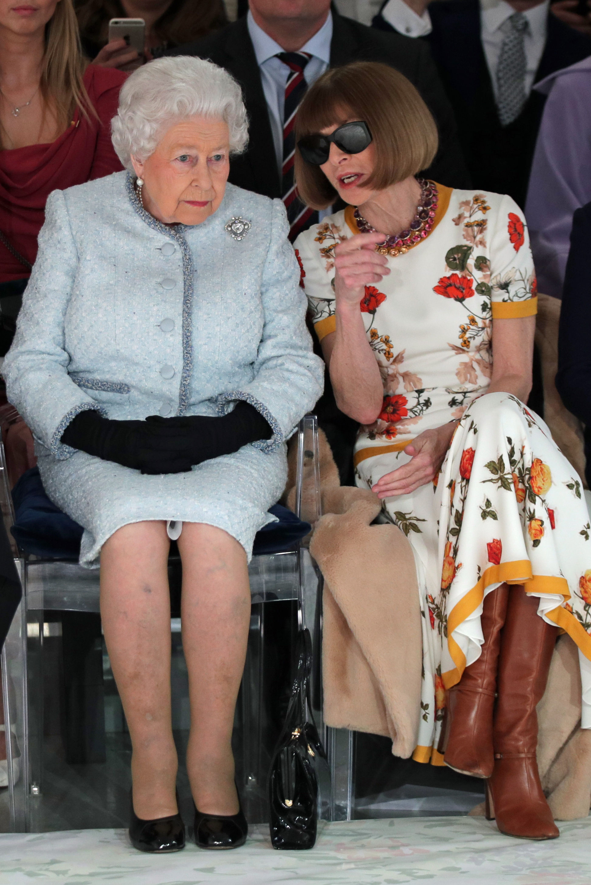 The Queen sits next to Anna Wintour, who is speaking