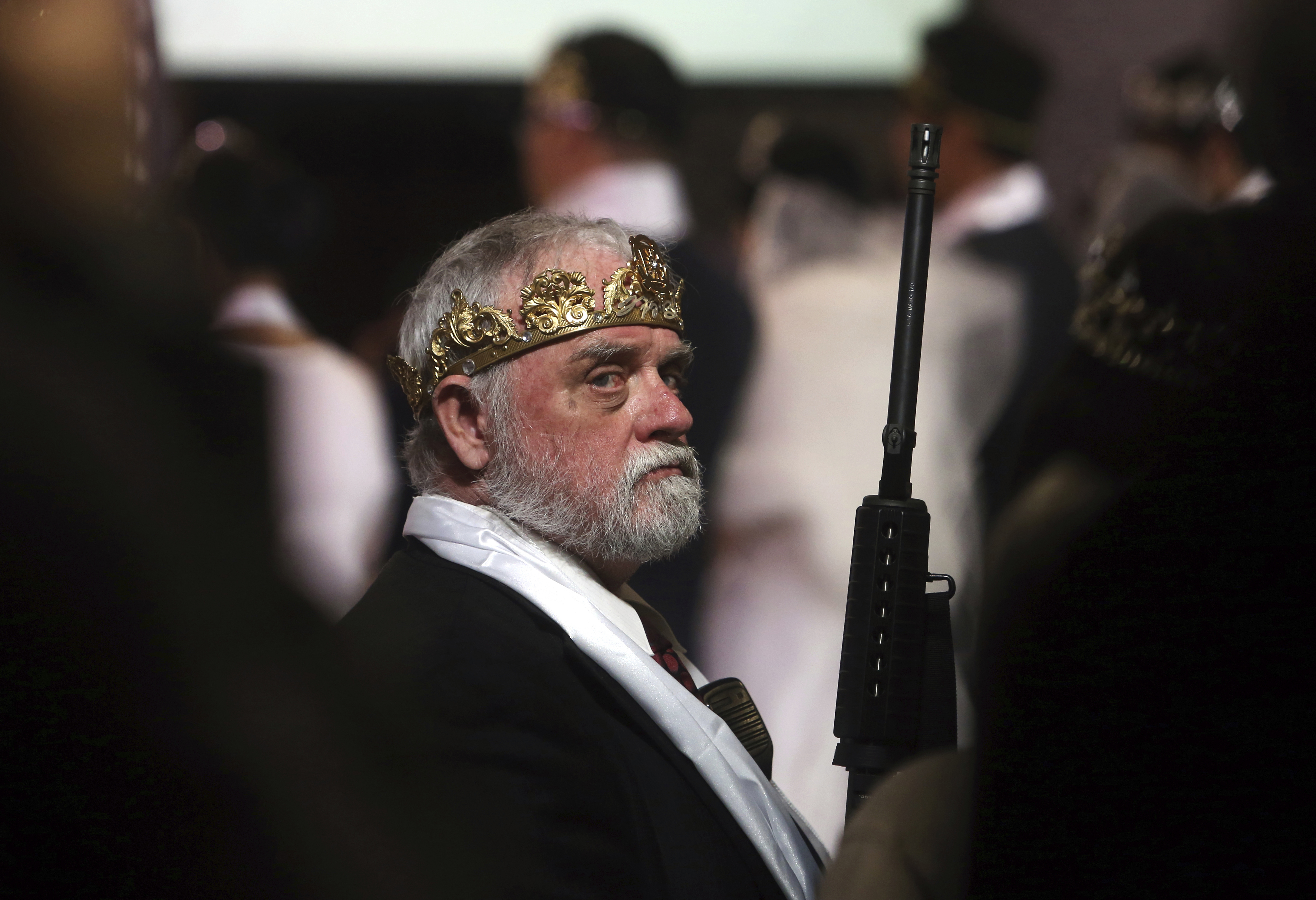 Man wears crown and holds rifle