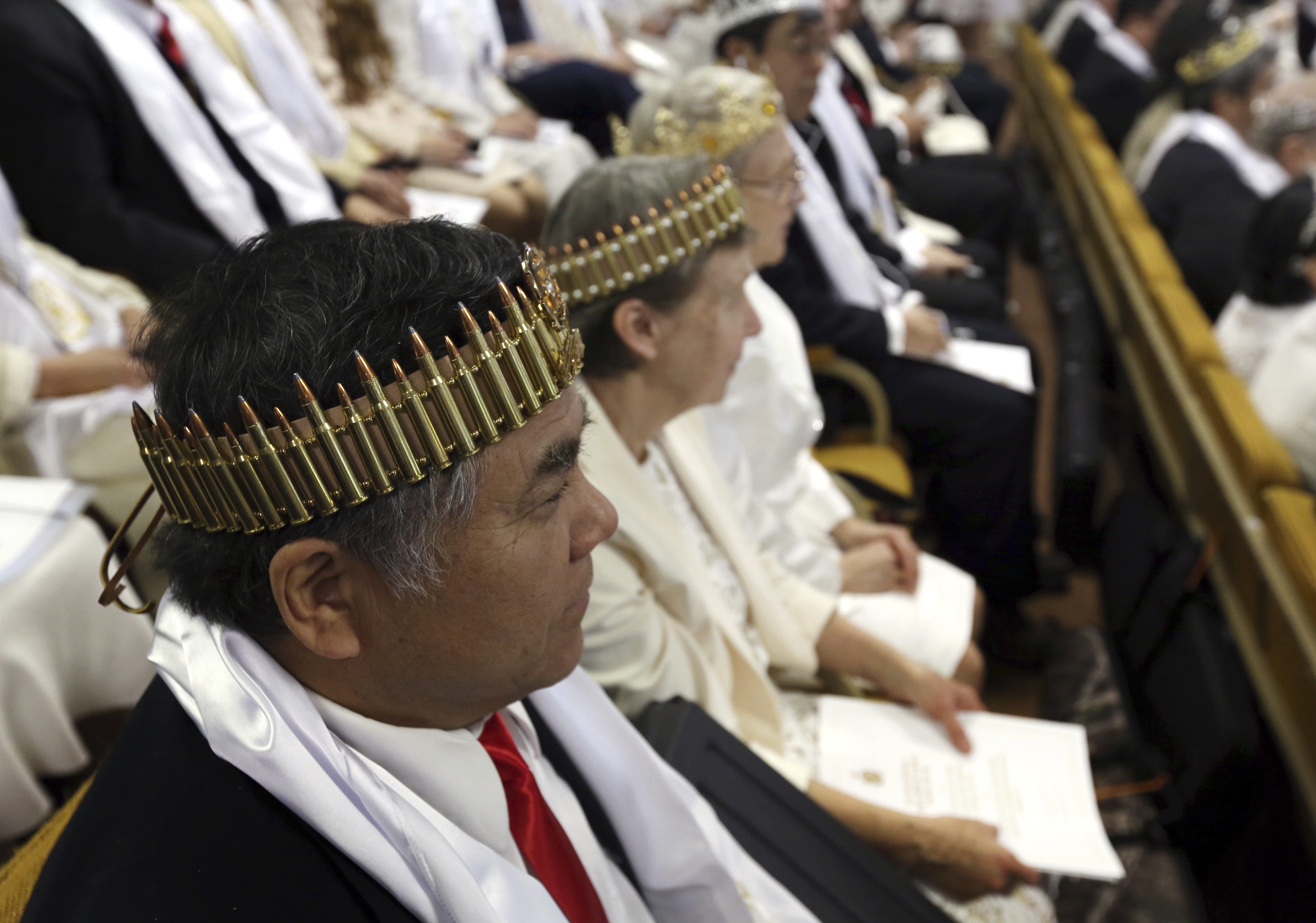 A man wears a crown of bullets at the ceremony (Jacqueline Larma/AP)