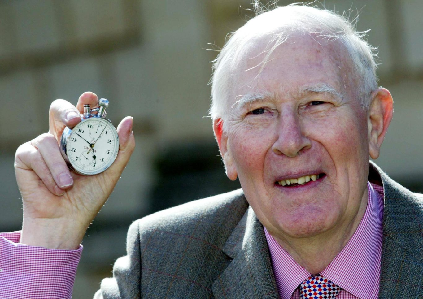 Sir Roger holds the stop-watch that recorded his sporting feat (Mark Lees/PA)