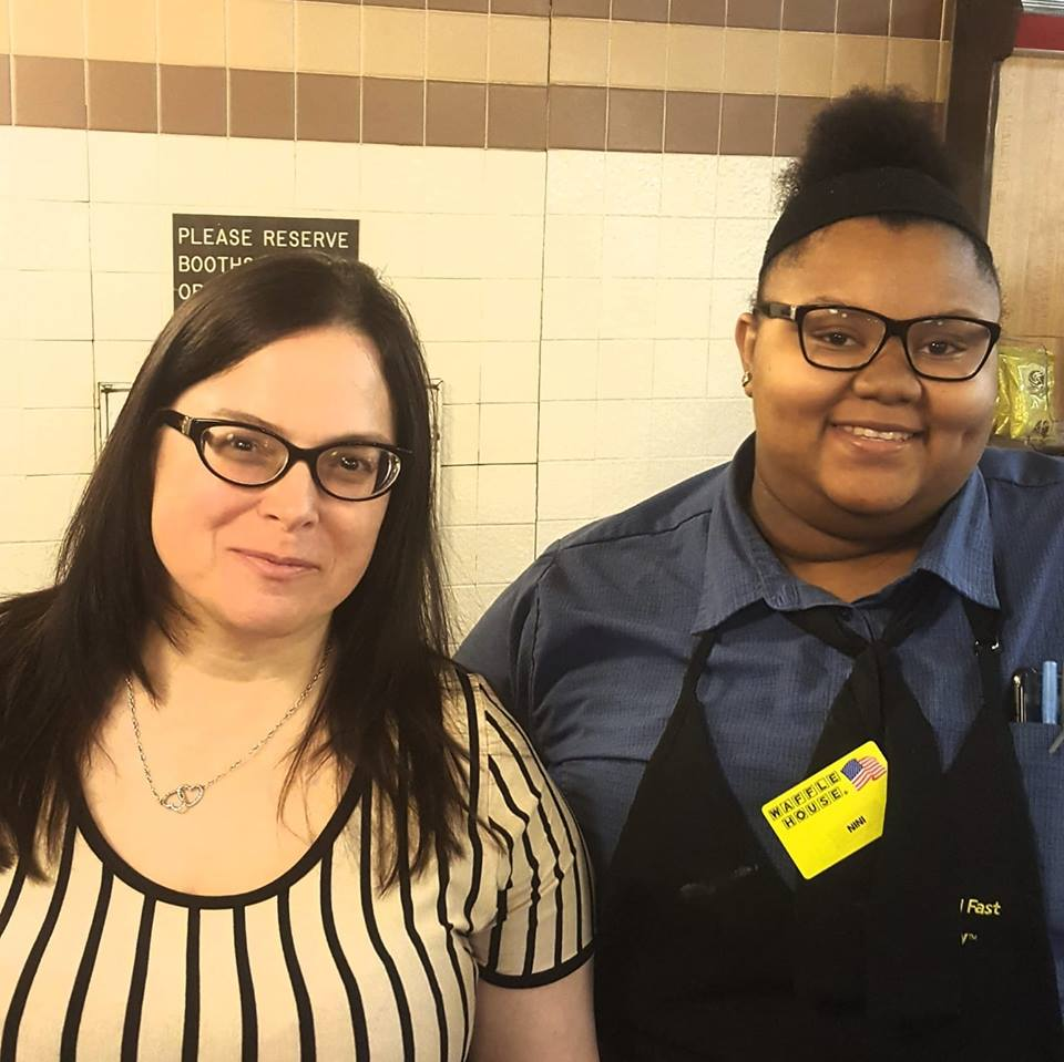 Waffle House employee helps elderly man cut up his food class=