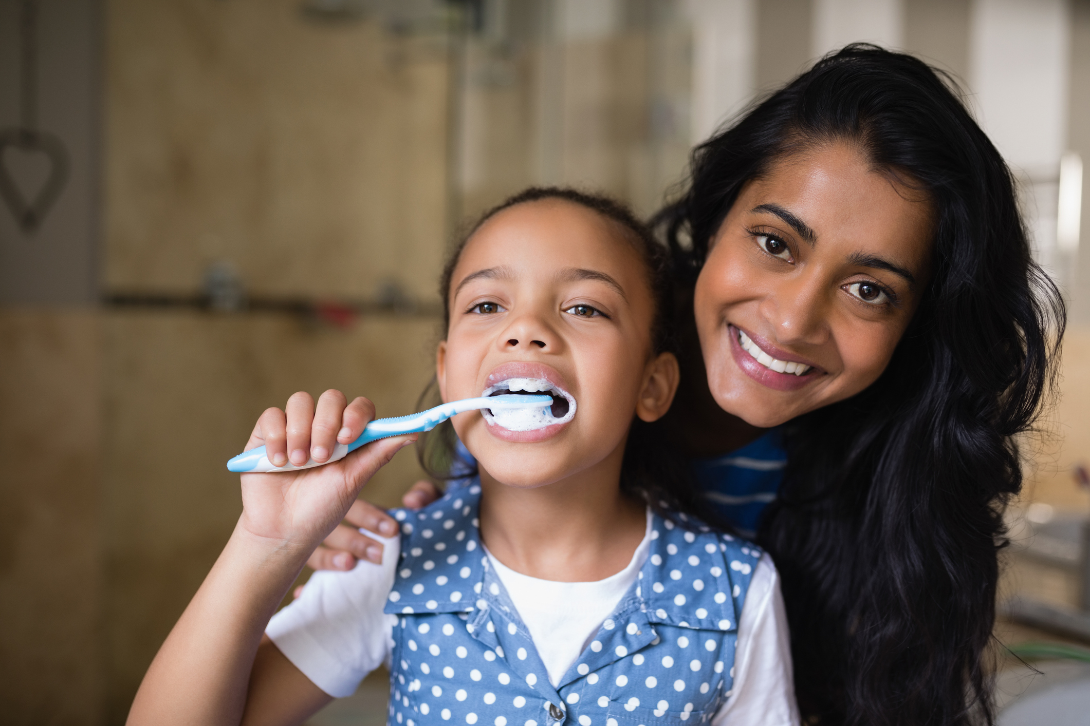 Close up of girl brushing teeth with mother in bathroom