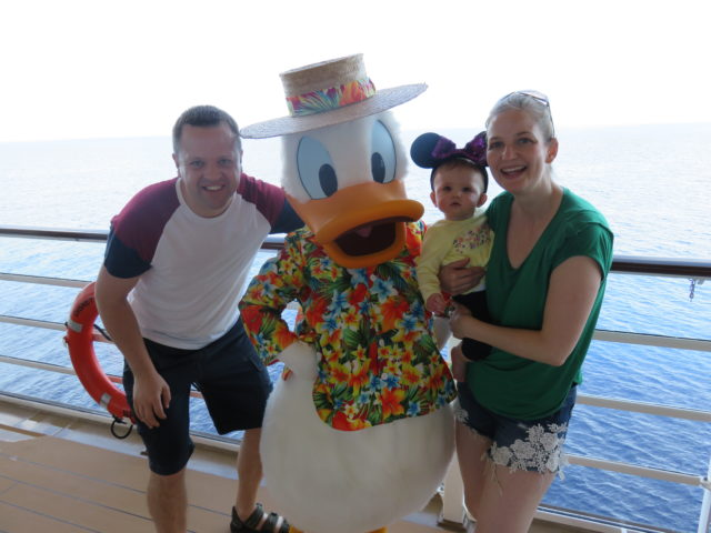 Wesley Johnson with his wife Carla and daughter Evie meet Donald Duck on the Disney Dream.
