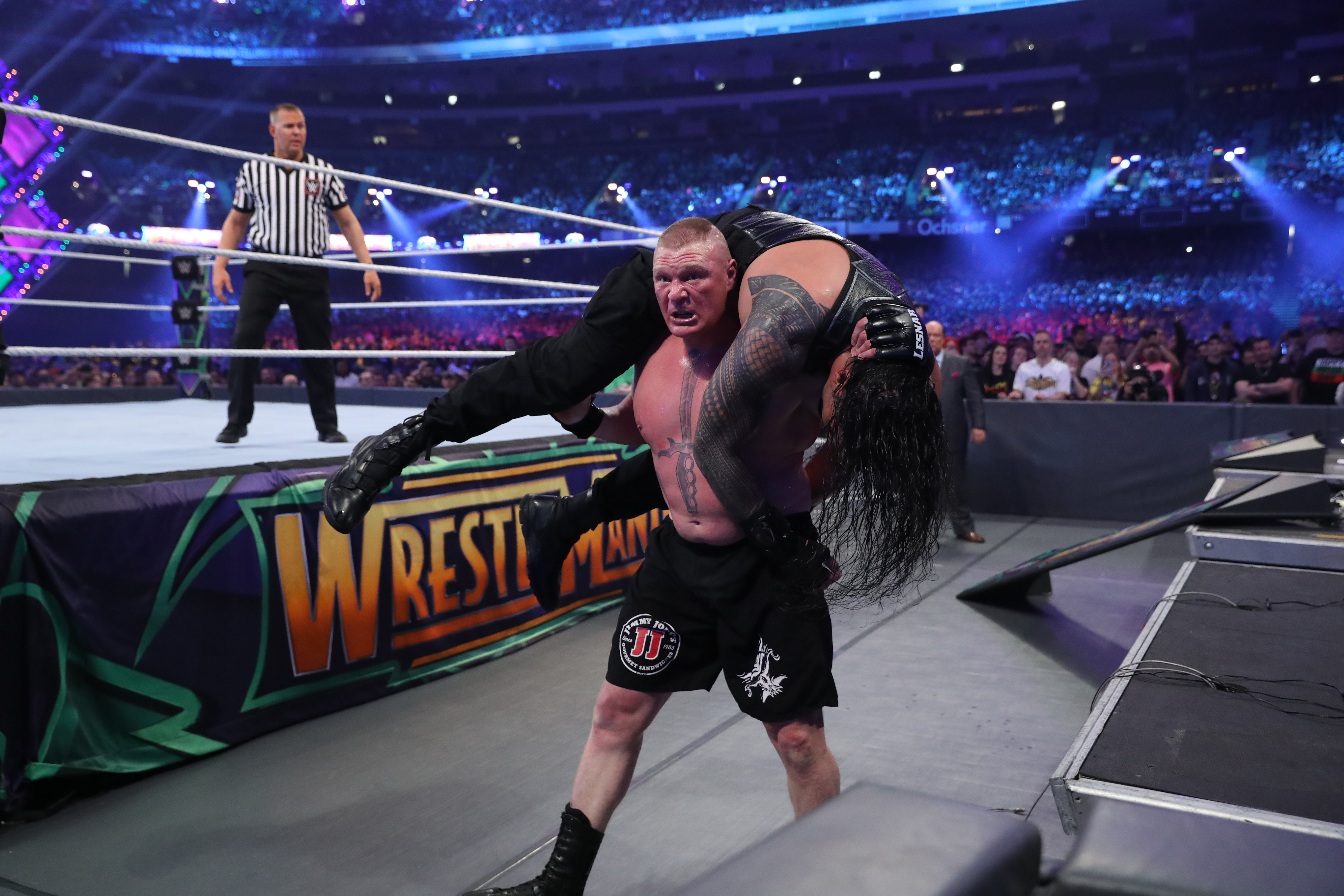 Lesnar with Reigns on his back