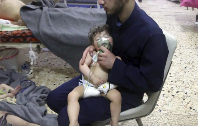 A medical worker giving toddlers oxygen in Douma