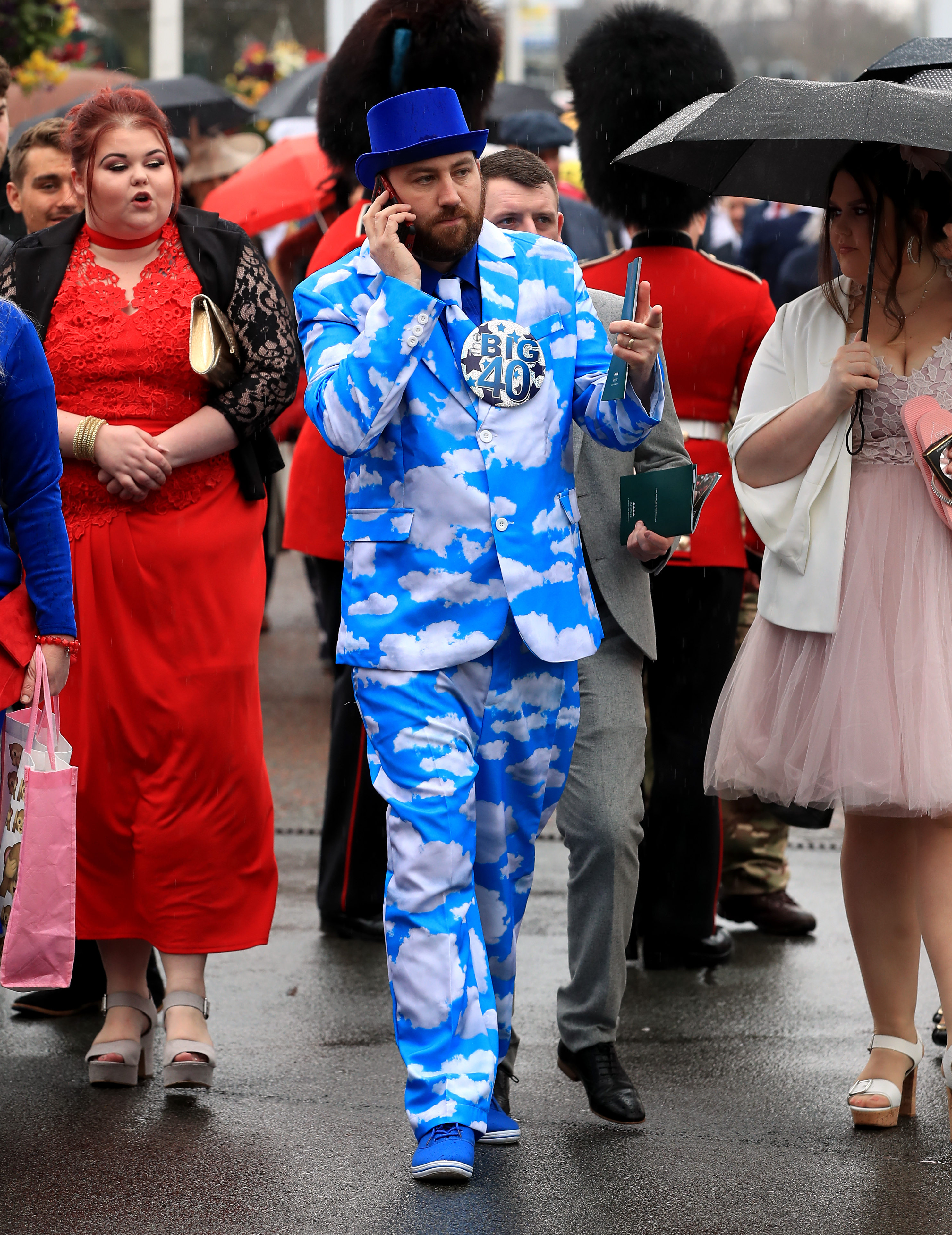 A racegoer wearing a suit adorned with clouds on his 40th birthday during Ladies Day of the 2018 Randox Health Grand National Festival at Aintree Racecourse, Liverpool.