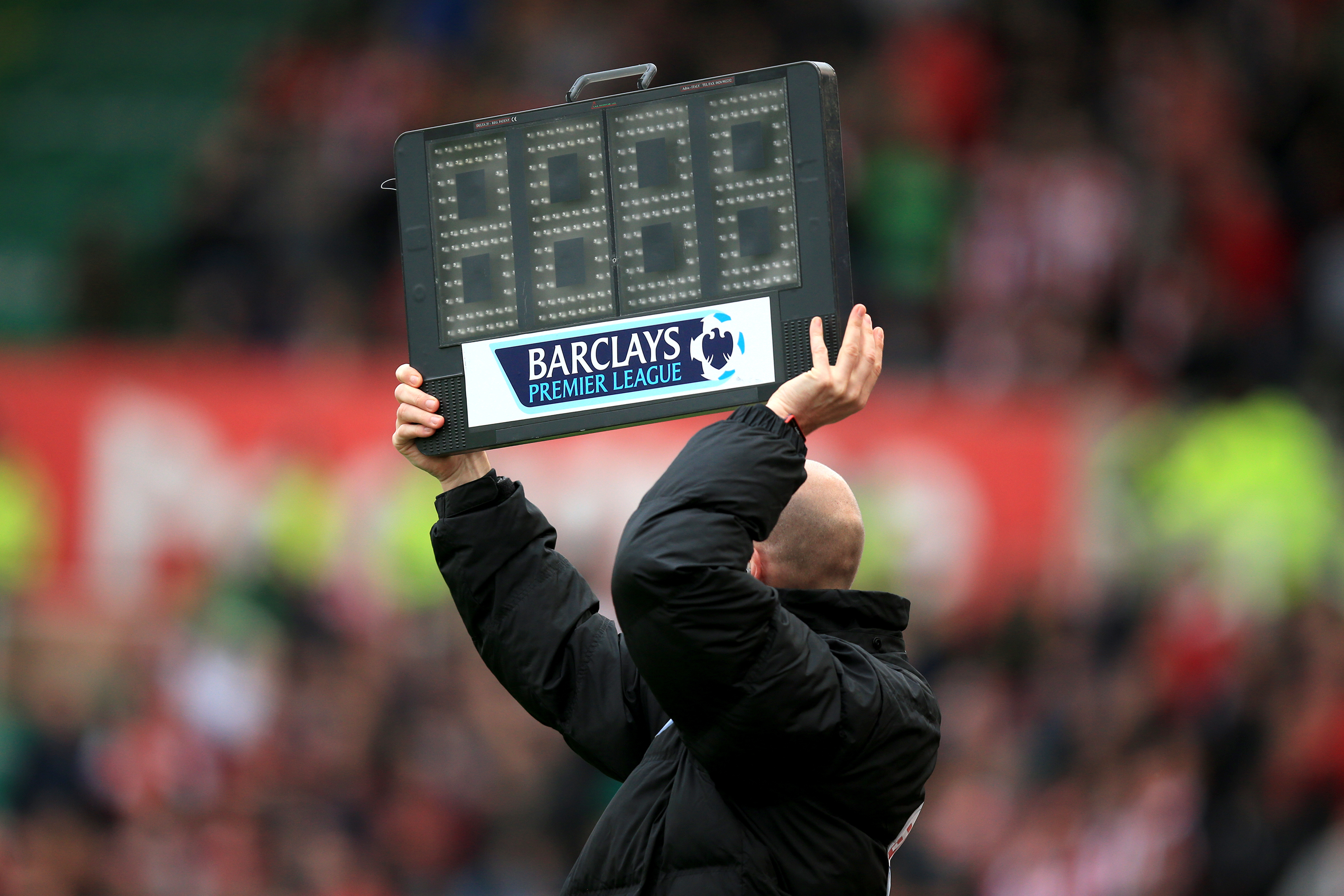 The fourth official holds up the board to signify added time
