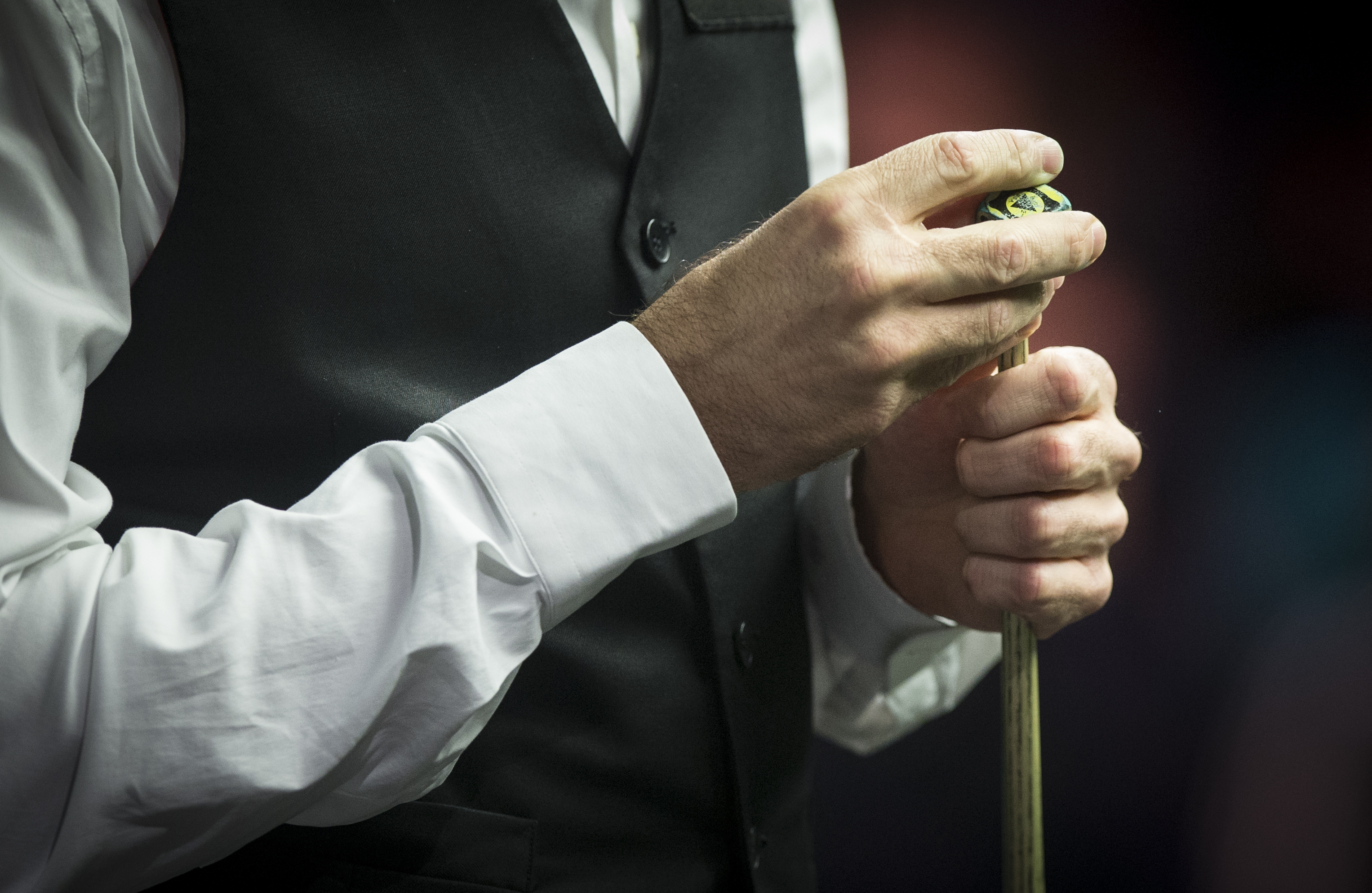 A snooker player chalks their cue