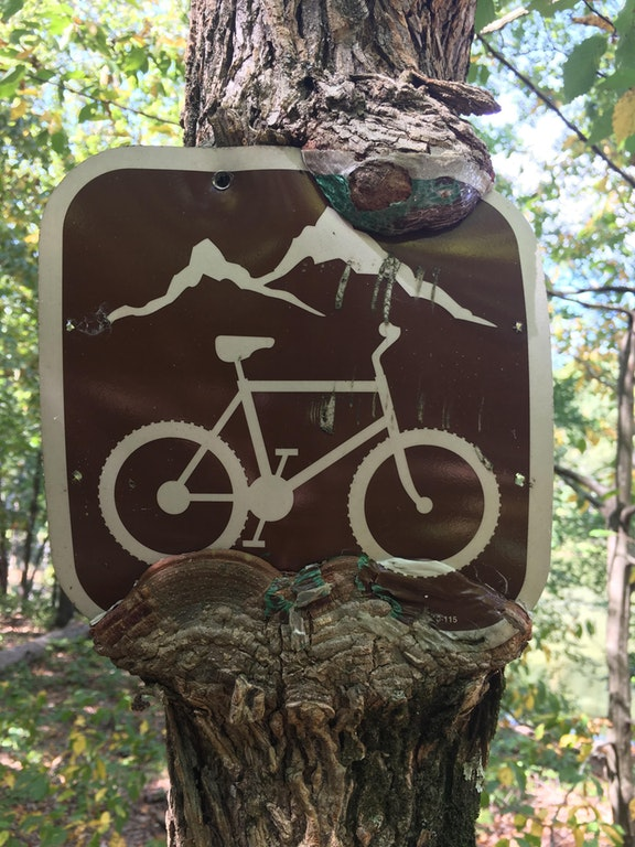 A cycling sign with paint coming off