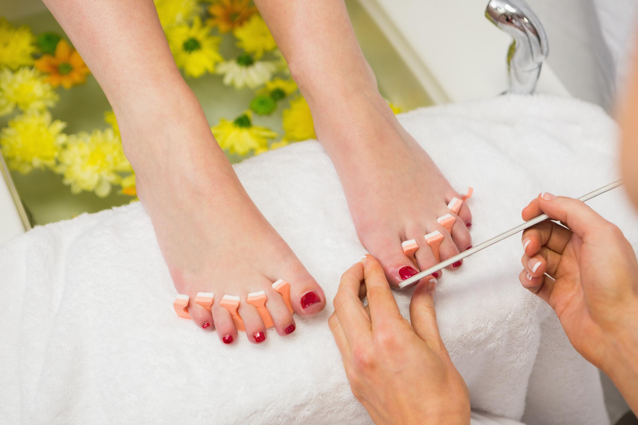 Closeup of woman polishing toe nails at spa center