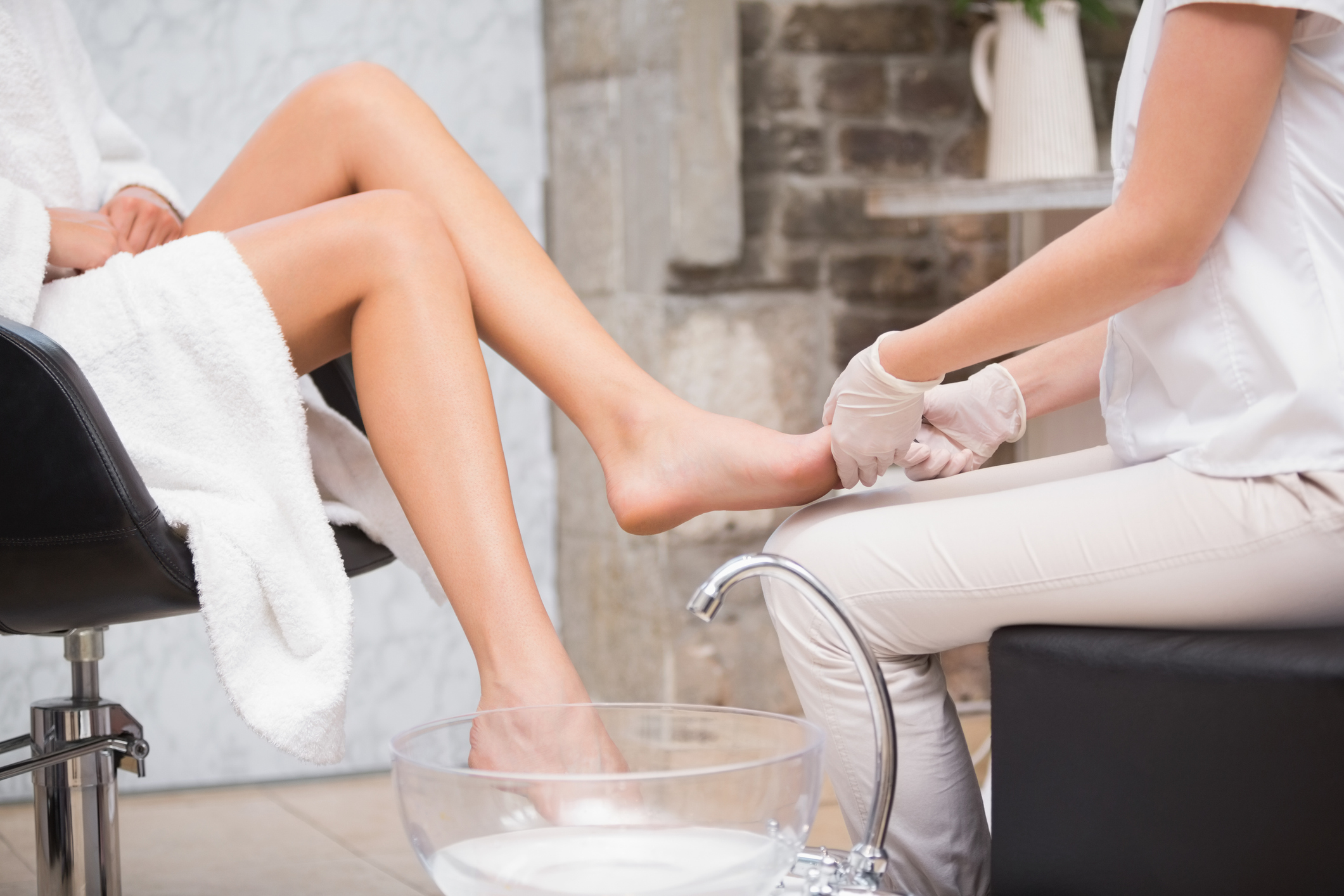 Woman getting a pedicure from beautician at the beauty salon