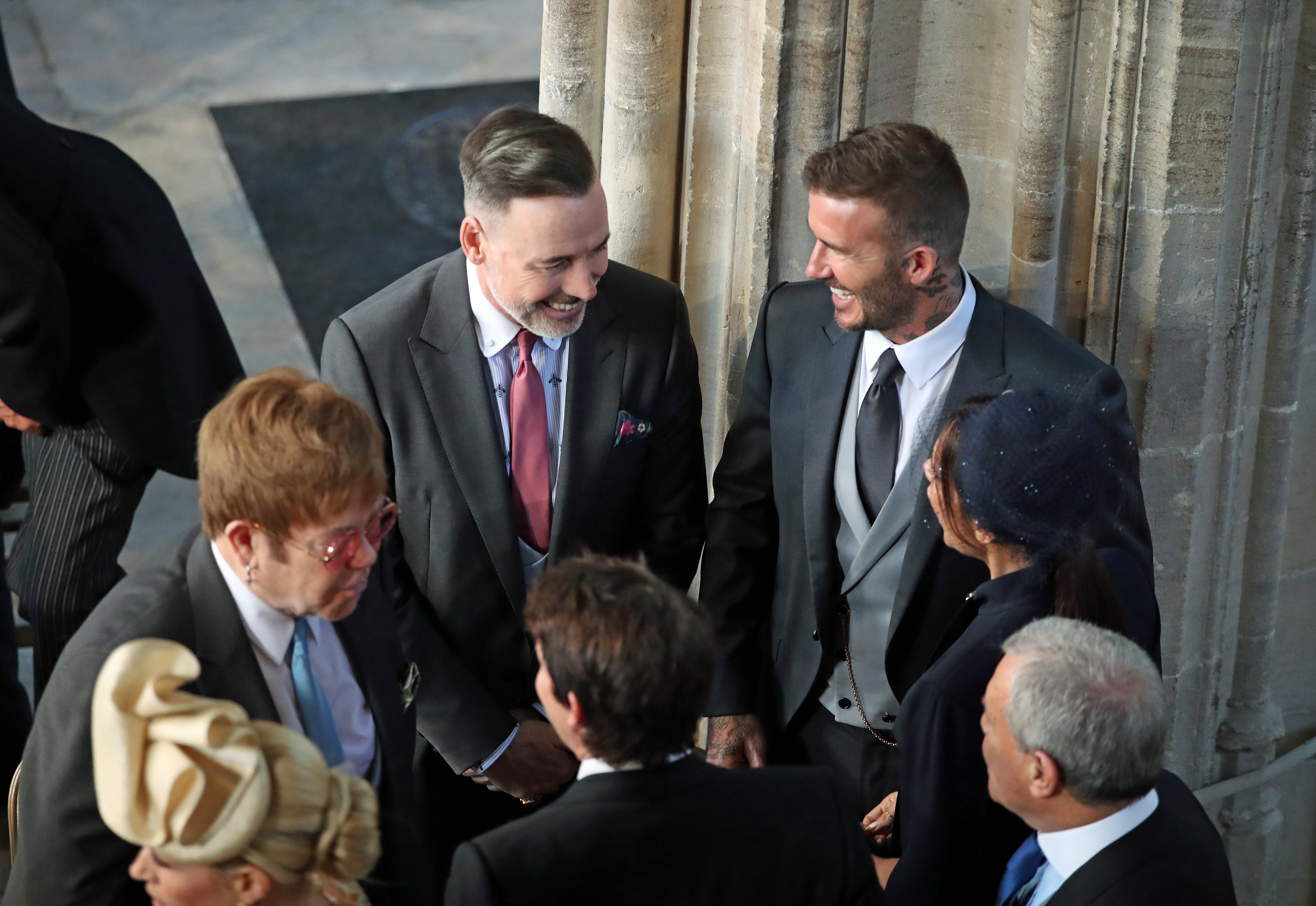 David and Victoria Beckham (both right) talk with Sir Elton John (left) and David Furnish as they arrive in St George's Chapel at Windsor Castle for the wedding of Prince Harry and Meghan Markle.