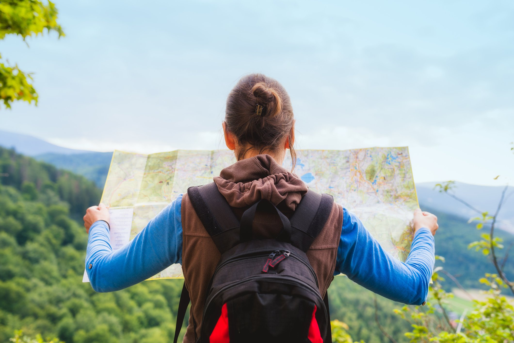 backpacker checks map to find directions