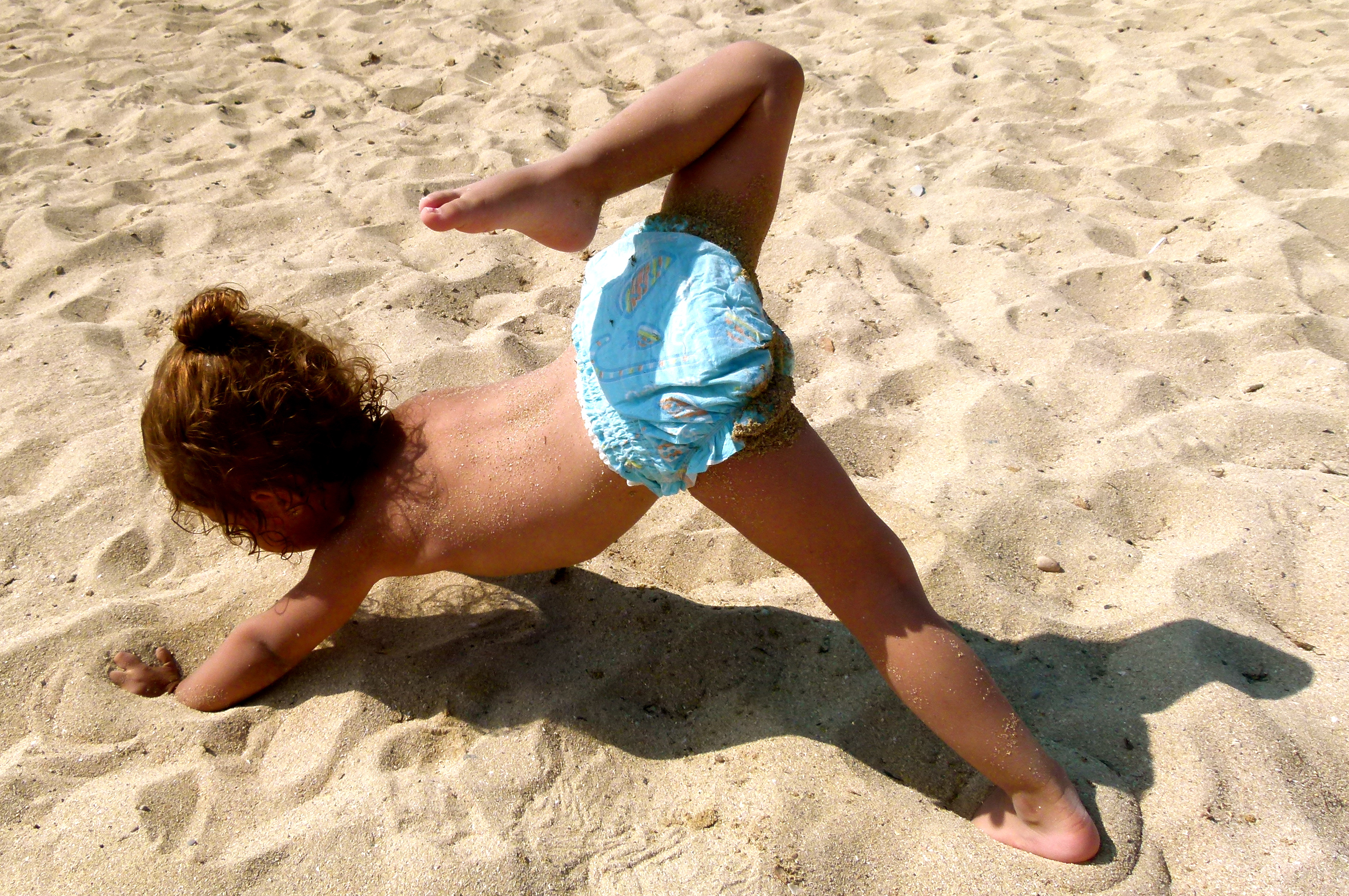Toddler in nappy on the beach doing yoga