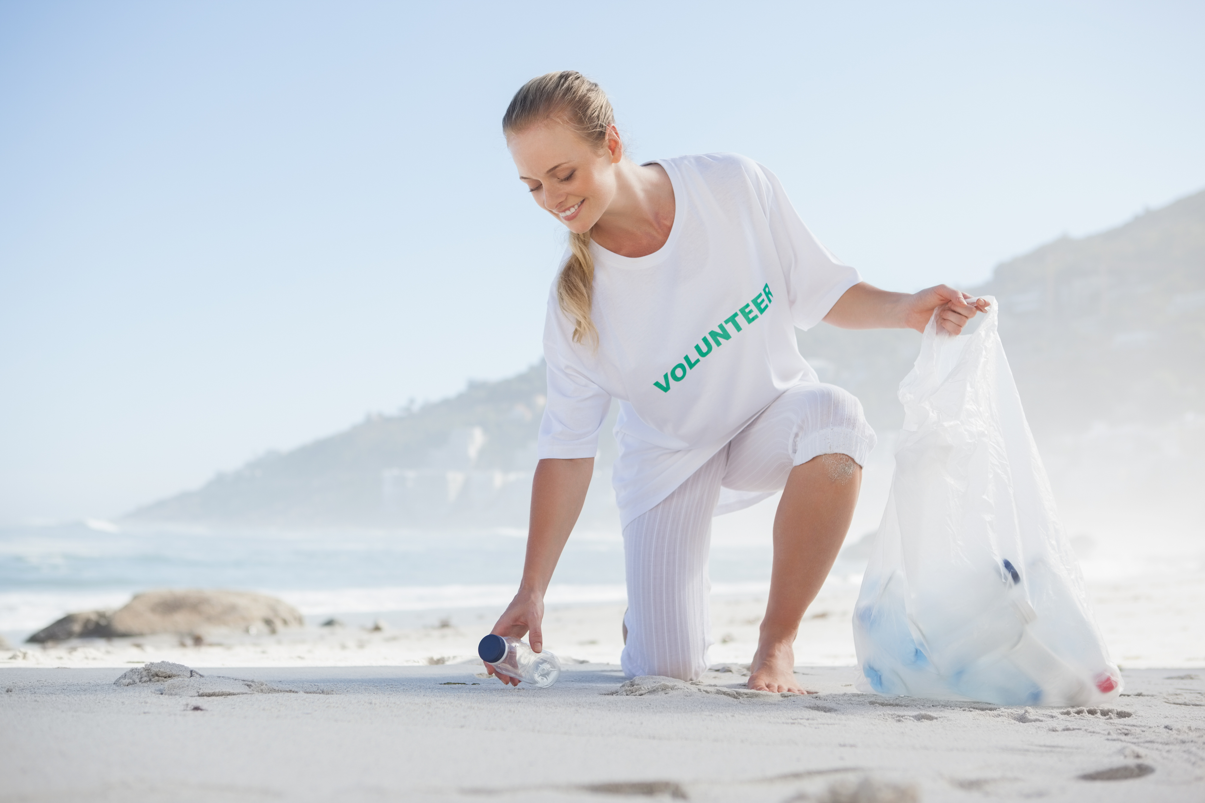 Blonde activist picking up trash on the beach
