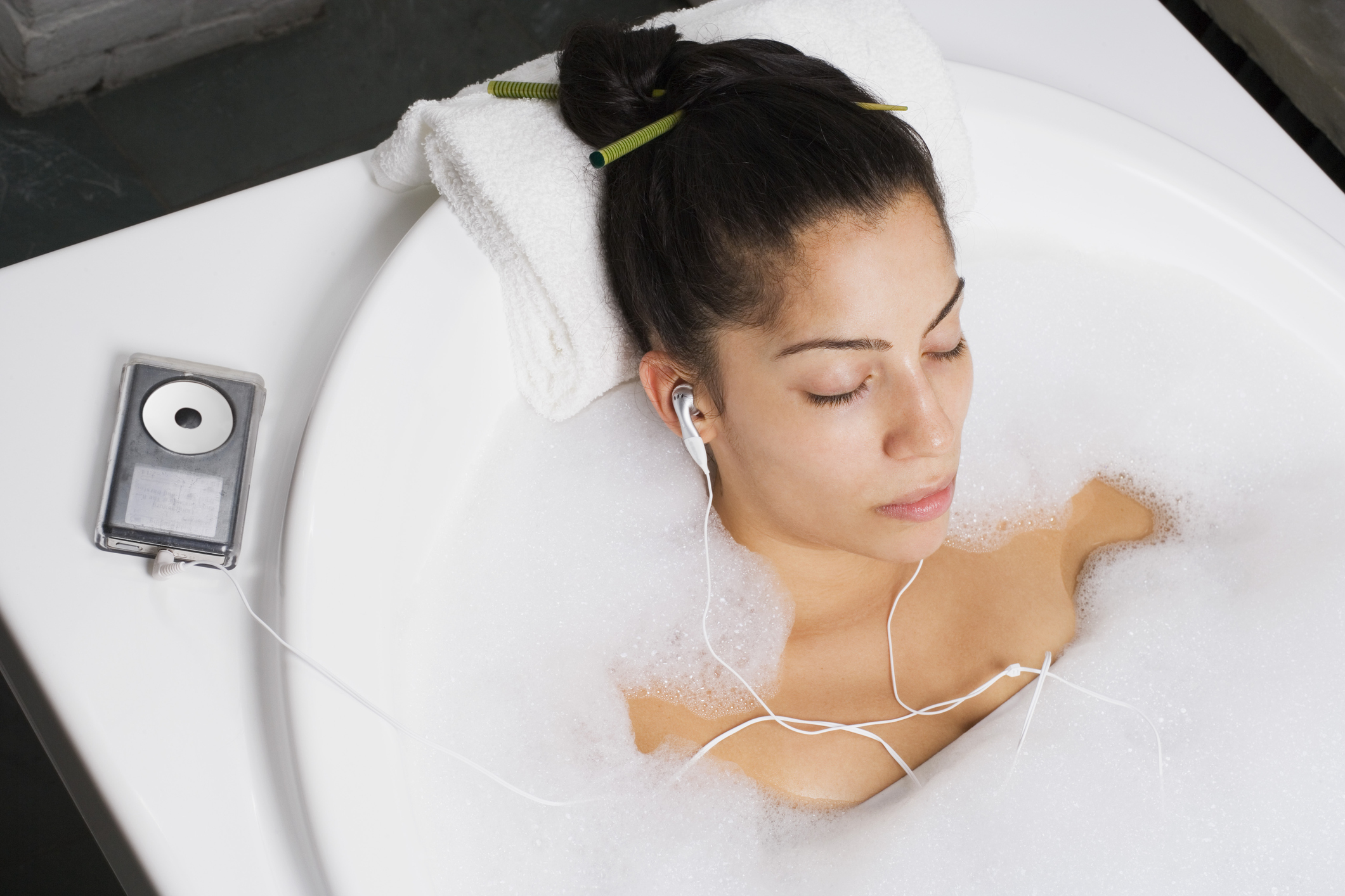 Woman relaxing in bubble bath with music