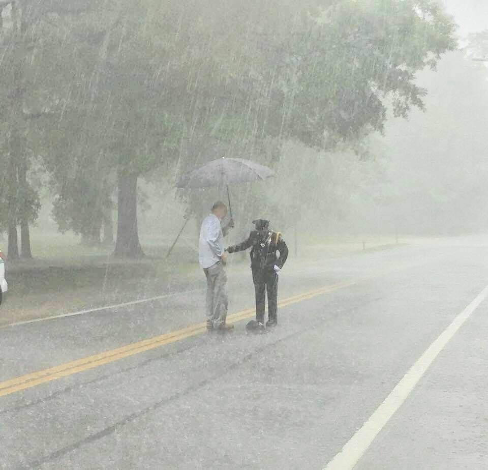 Mr Hammett holding an umbrella over an officer assisting a snapping turtle in heavy rain