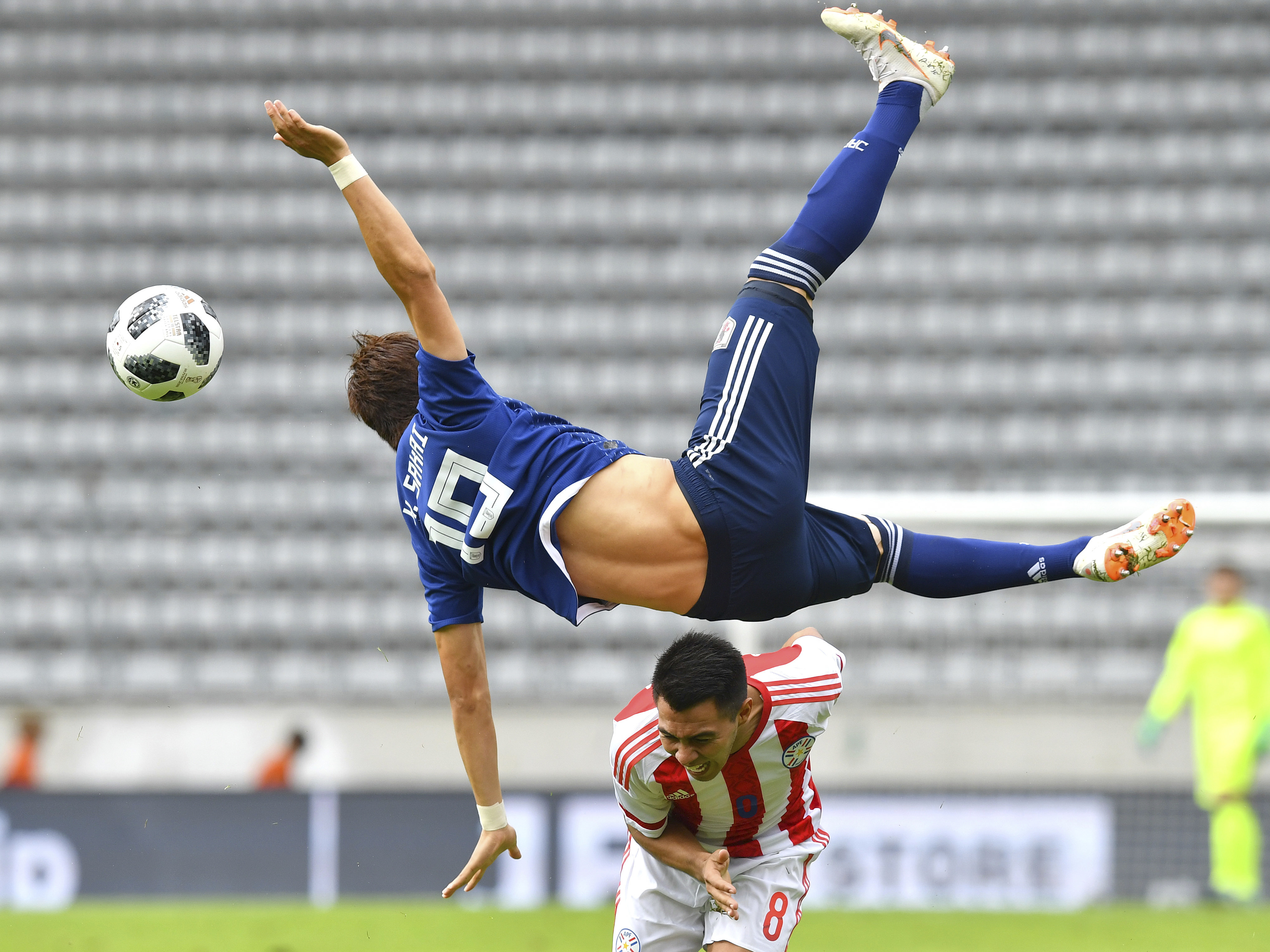 Japan's Shinji Kagawa leaps for the ball against Paraguay