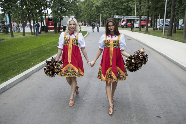 Two women dressed in Russian traditional costumes walk near the Luzhniki Stadium