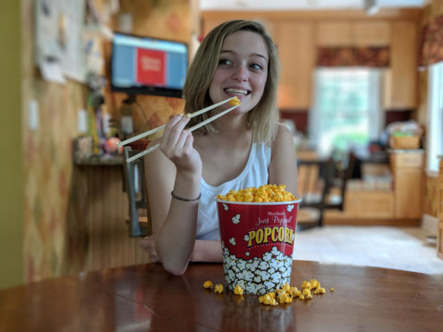 Eating popcorn with chopsticks.