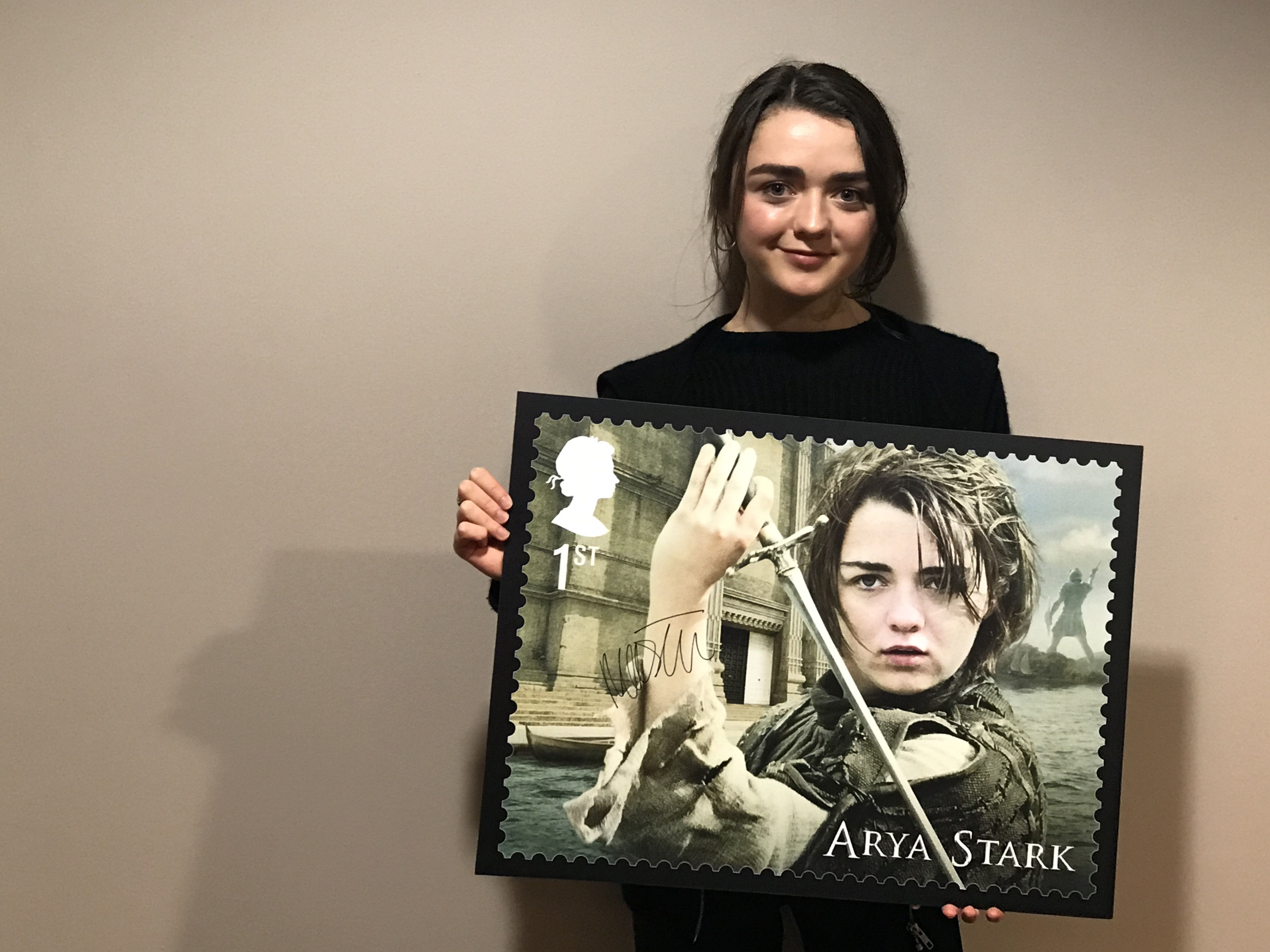 Maisie Williams holding up her enlarged stamp