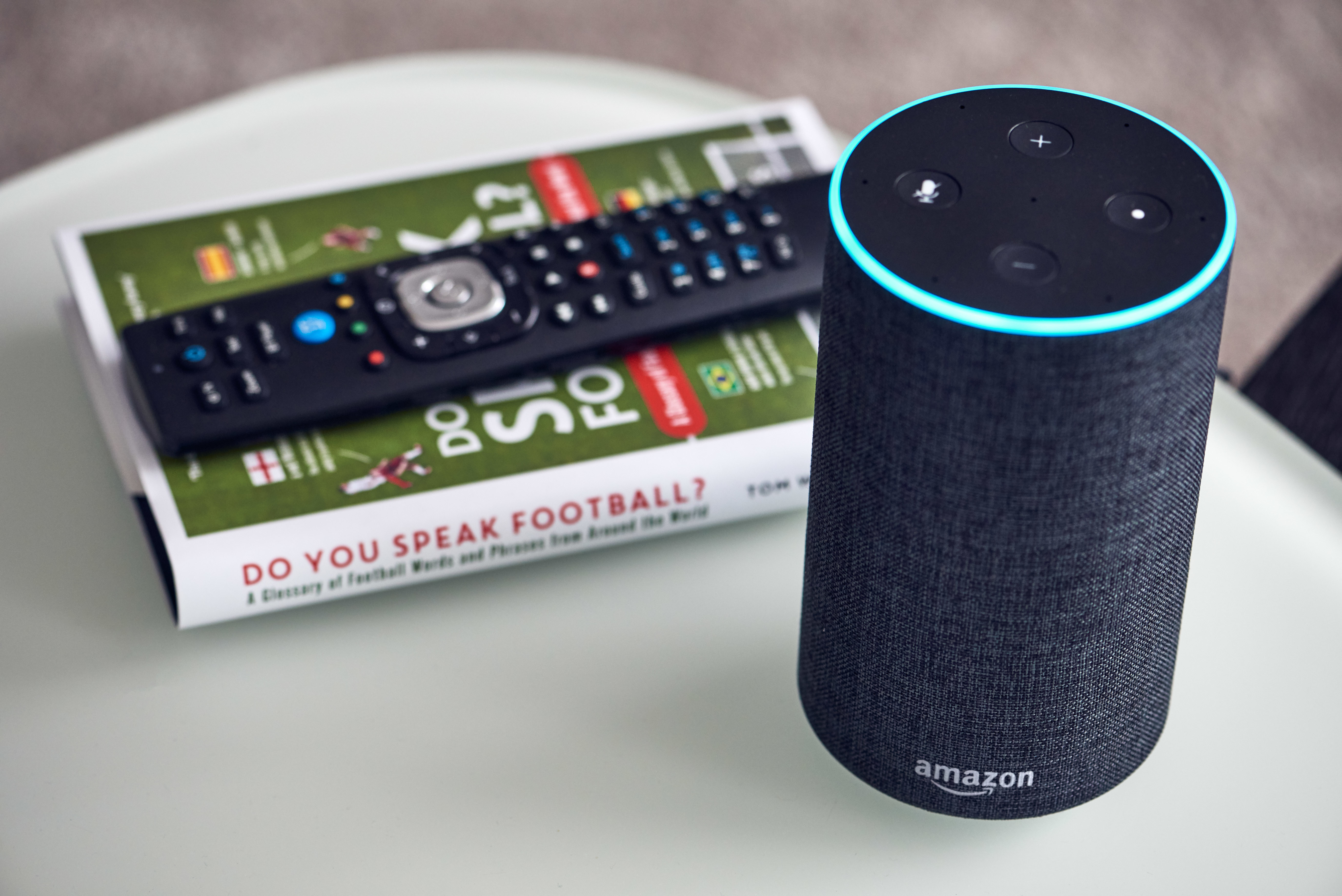 An Amazon Echo next to a book about football