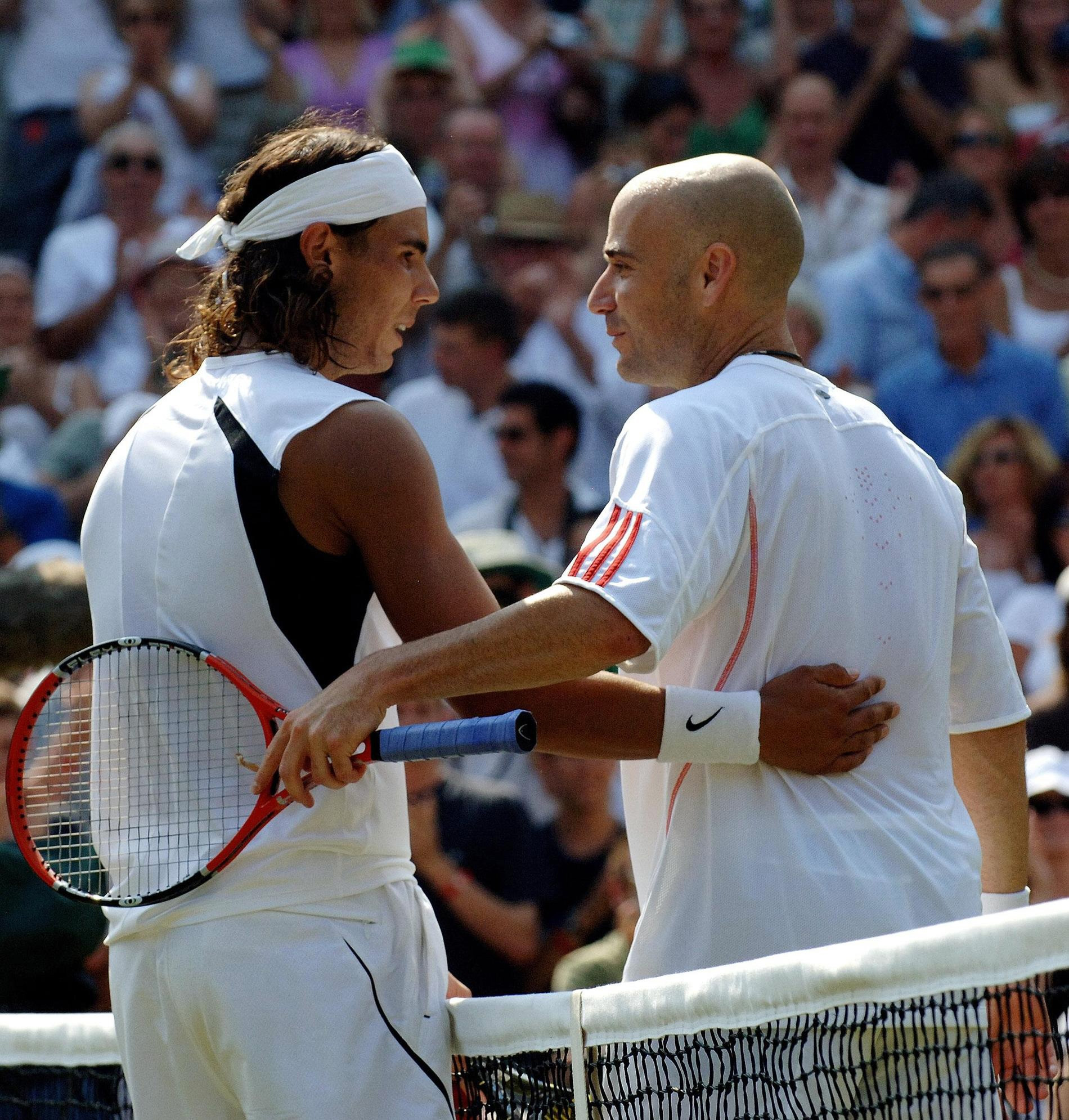 Spain's Rafael Nadal consoles Agassi after a defeat at Wimbledon in 2006. (Fiona Hanson/PA)