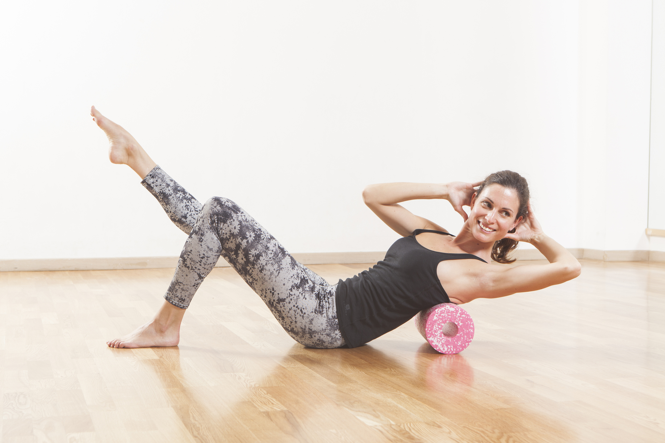 Beautiful woman pilates instructor stretching and warming up using foam roller