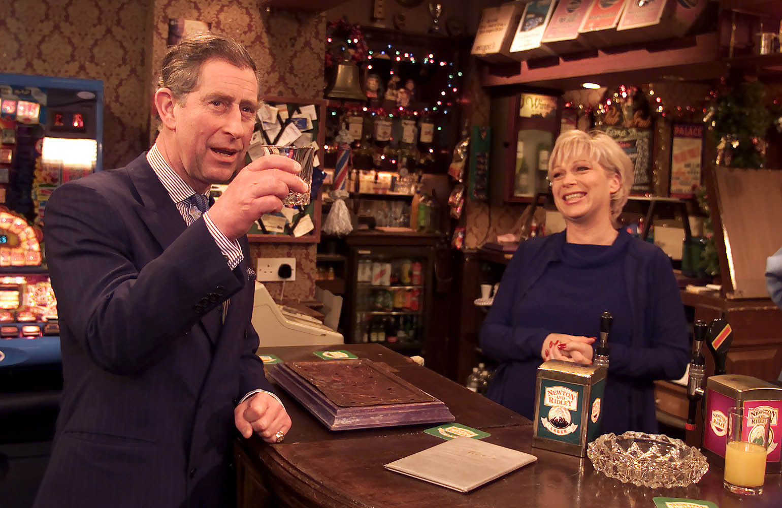 The Prince of Wales enjoys a scotch with Coronation Street's barmaid Natalie Barnes, played by Denise Welch (Phil Noble/PA)