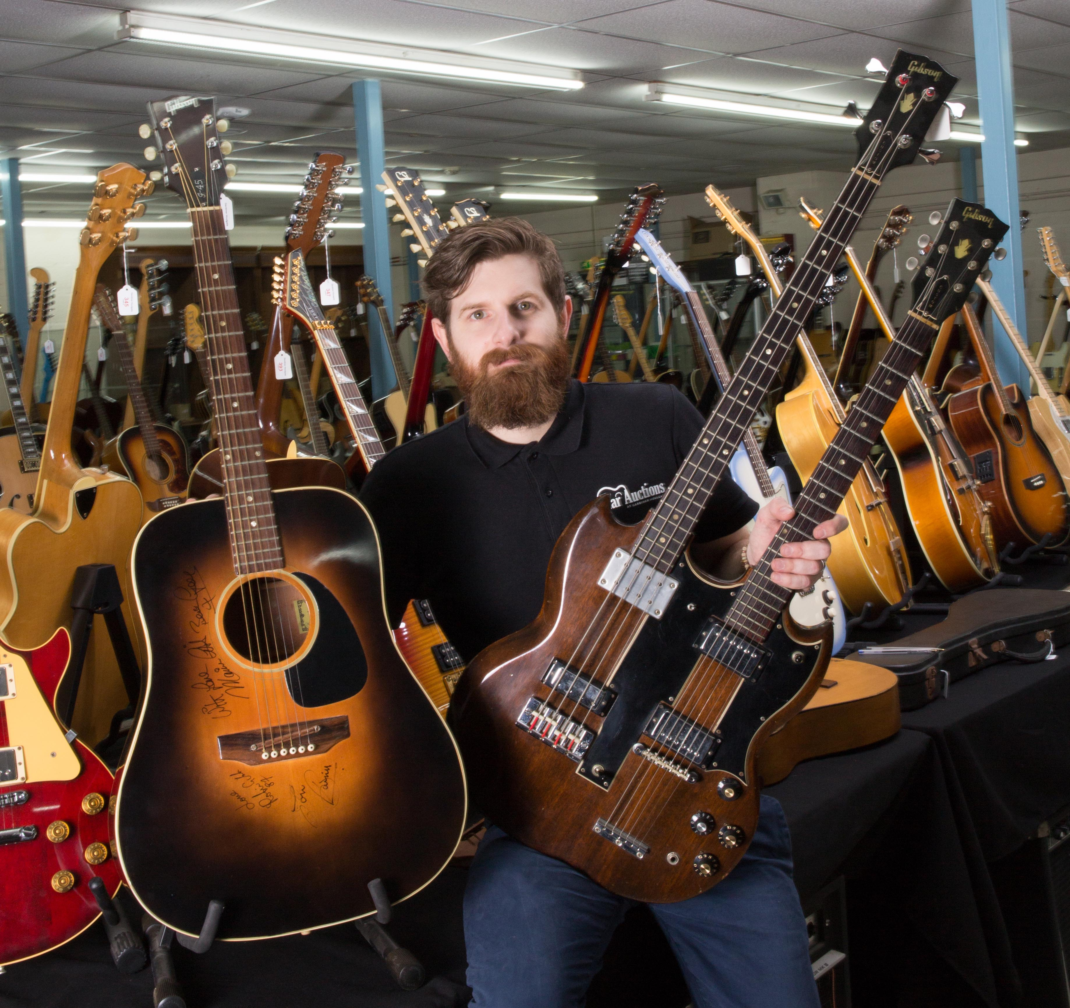 Luke Hobbs, of Wiltshire-based auctioneers Gardiner Houlgate, with the Maurice Gibb-owned Gibson J45 (left) and Gibson doubleneck guitars (Clare Hobbs Photography/PA)