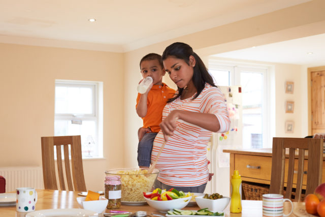 A pregnant woman cooks while holding her small child