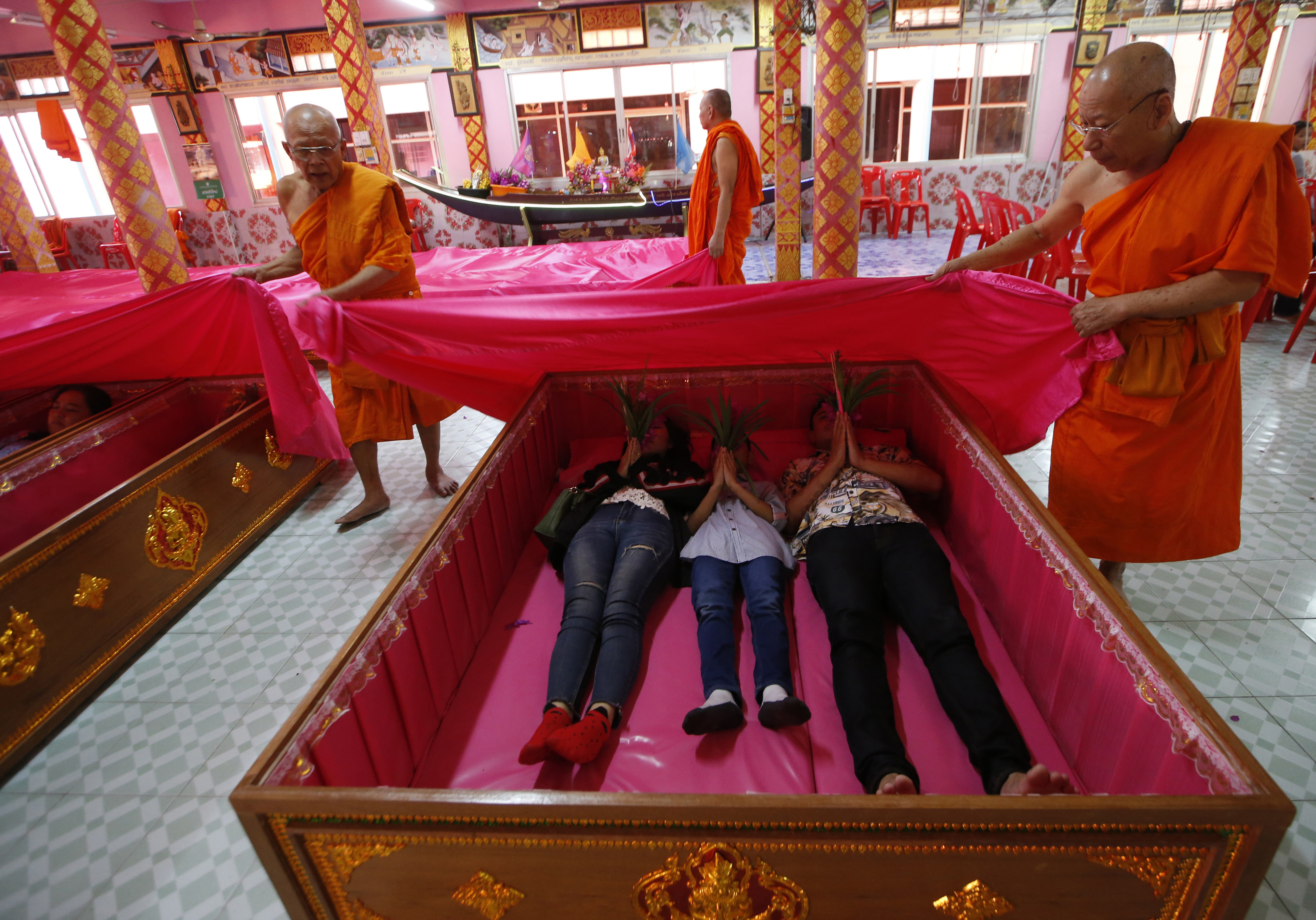 Monks cover worshippers lying in coffins