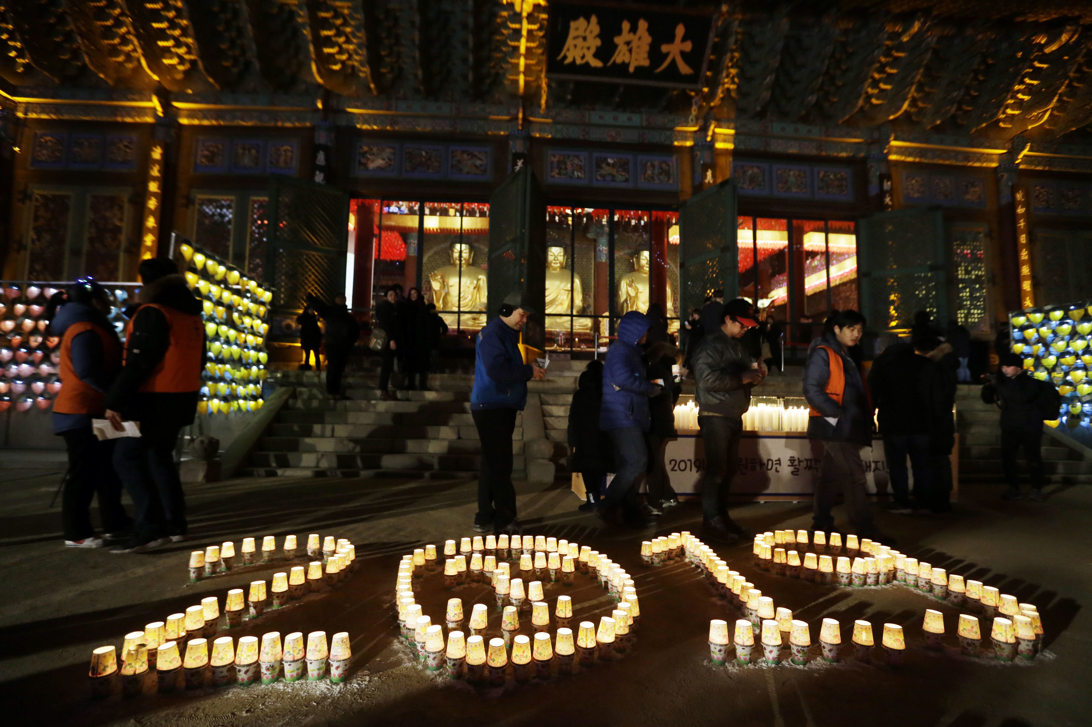 Buddhists light candles during New Year celebrations at Jogyesa Buddhist temple in Seoul
