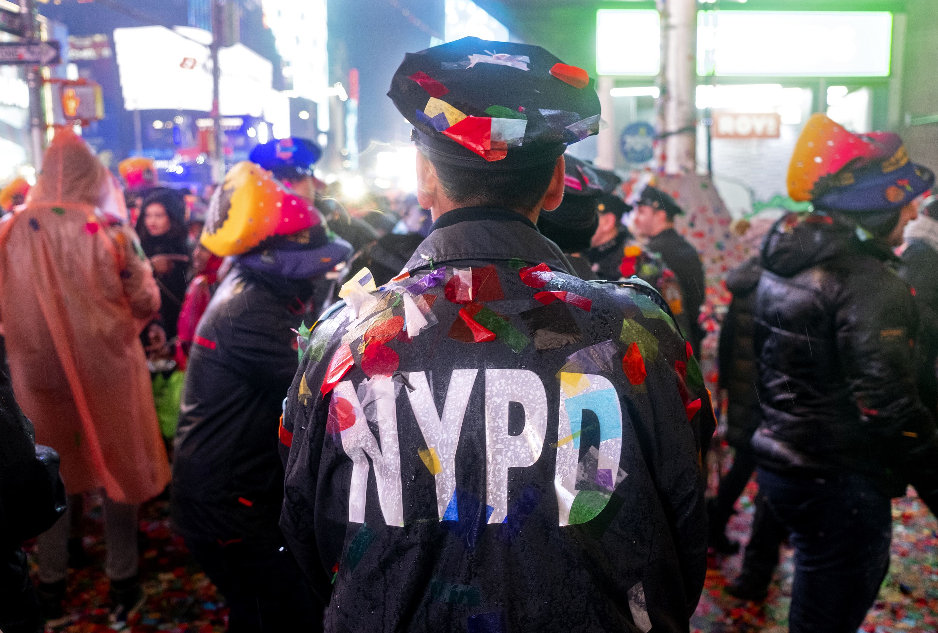 A New York City police officer is covered with confetti in Times Square
