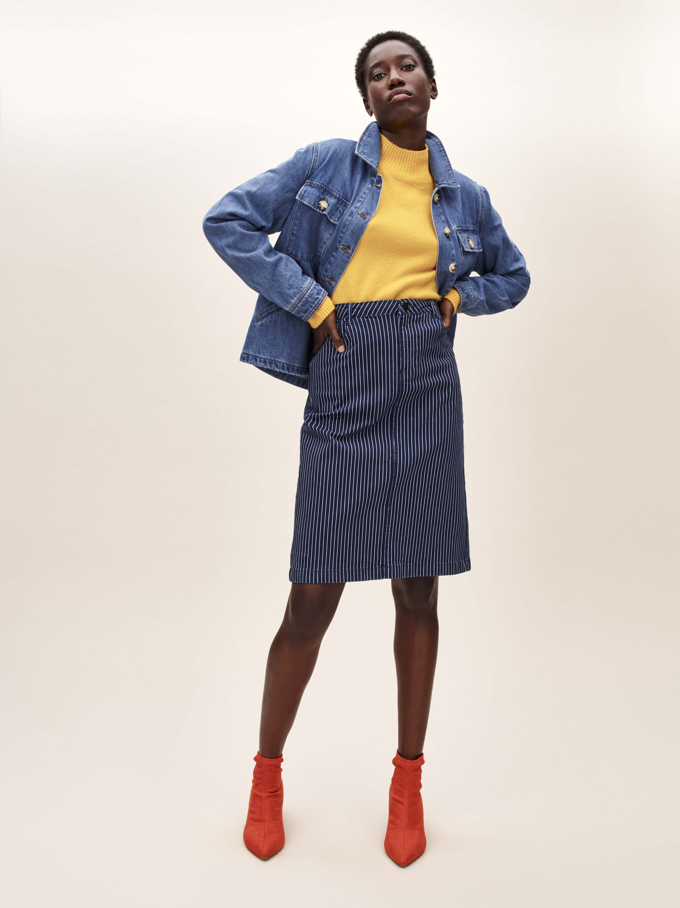 model weaing Tu at Sainsbury's Denim Jacket; Yellow Roll Neck Jumper; Stripe Pencil Skirt; Online Exclusive Orange Sock Ankle Boots