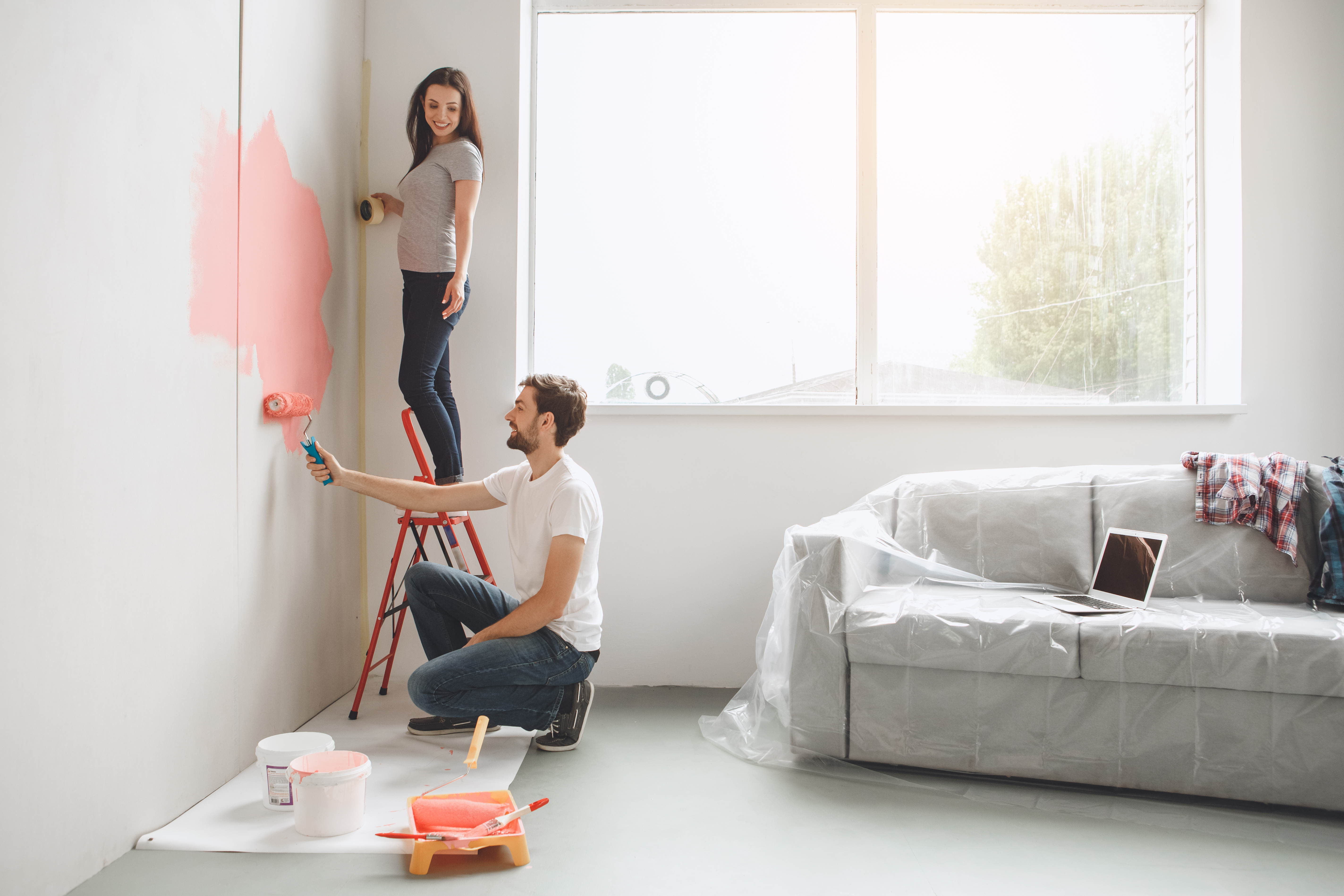 Couple repainting a wall