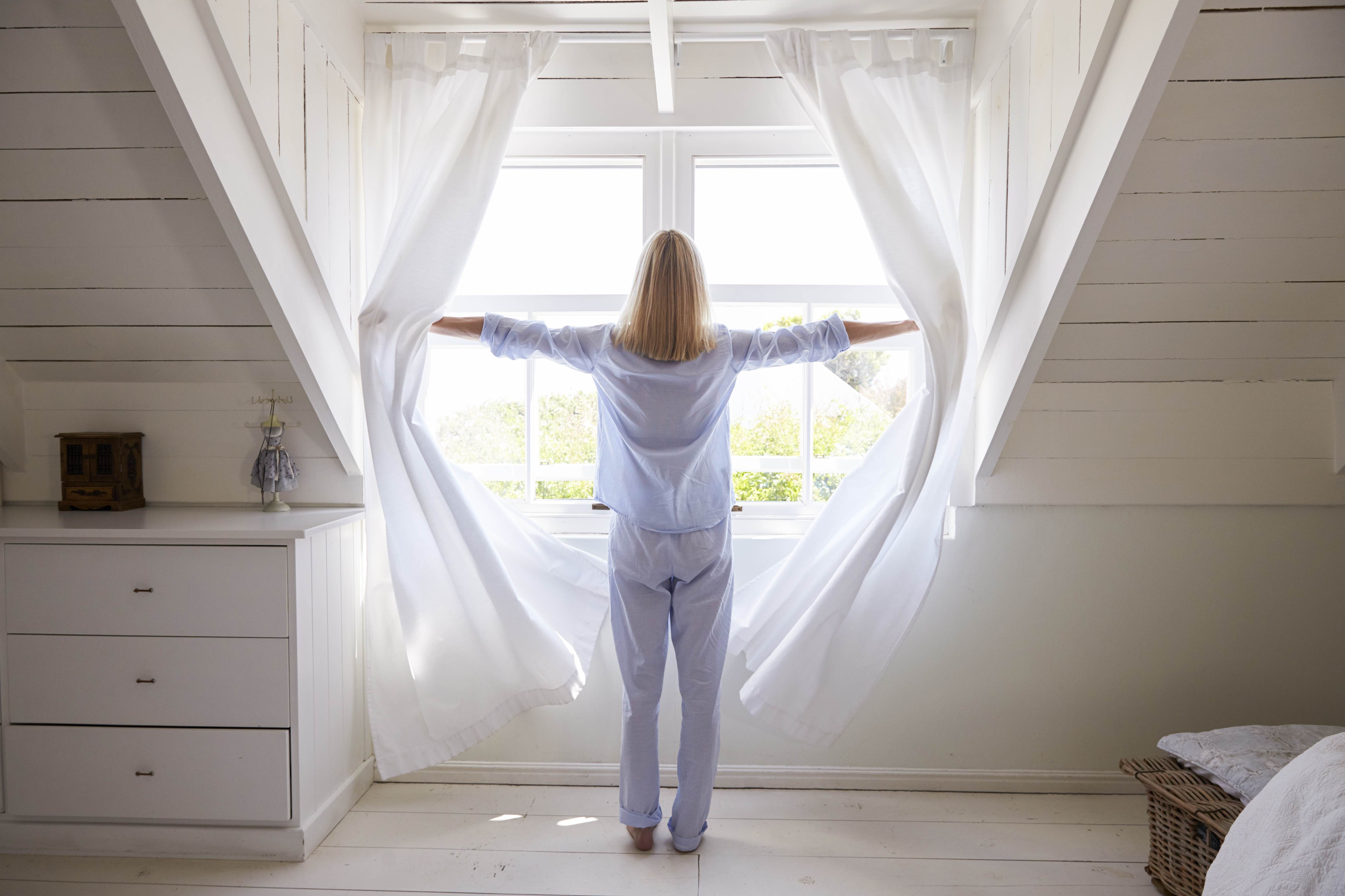 Rear View Of Woman Opening Curtains And Looking Out Of Window