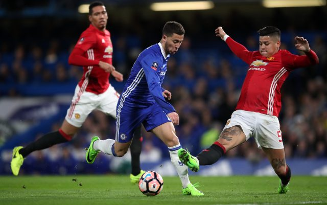 Marcos Rojo, right, challenges Chelsea's Eden Hazard