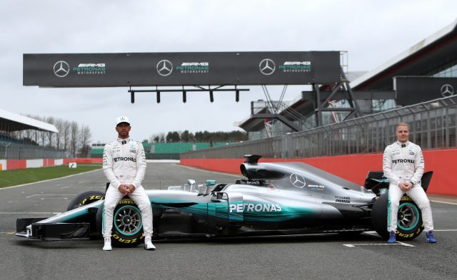 Lewis Hamilton, left, and Valtteri Bottas with a Mercedes car