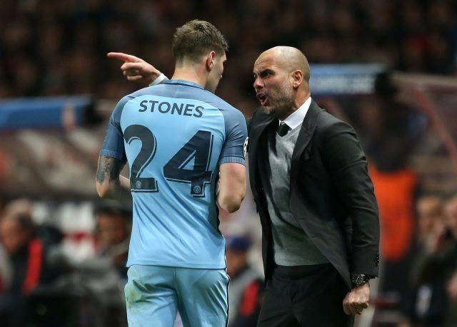 Pep Guardiola (right) gives instructions to Manchester City's John Stones