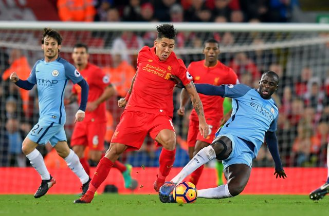 Liverpool's Roberto Firmino (left) and Manchester City's Yaya Toure battle for the ball