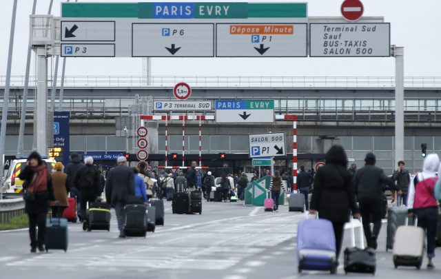 Passengers walk towards the airport after it reopened (Thibault Camus/AP)
