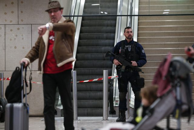 A riot police officer patrols inside Orly airport, south of Paris, as flights begin to resume