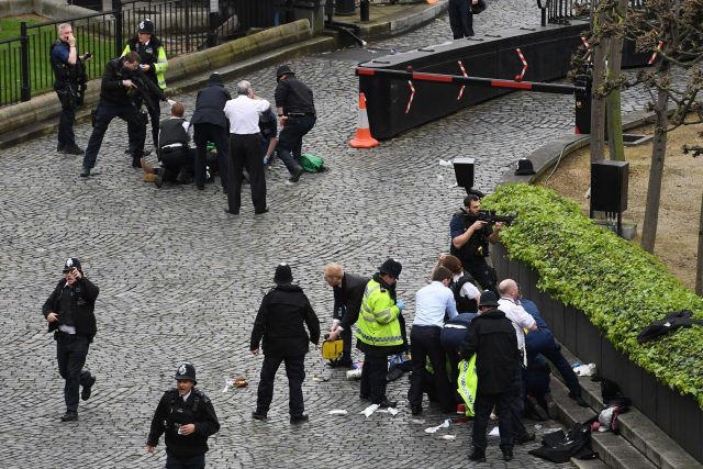 A policeman points a gun at a man on the floor at the top of the frame as emergency services attend the scene outside the Palace of Westminster, London (Stefan Rousseau/PA)