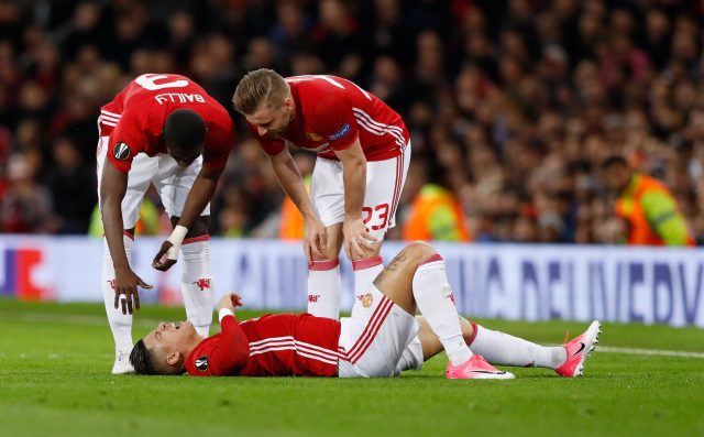Manchester United's Marcos Rojo lies injured
