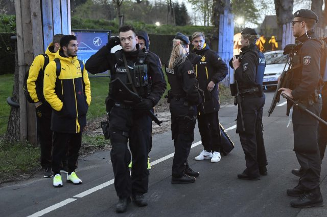 Dortmund's Marcel Schmelzer, talks to officers outside the team bus