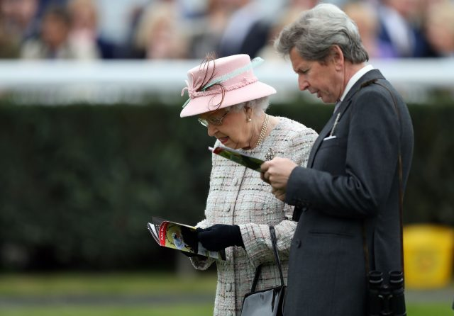 Queen Elizabeth II and her Bloodstock and Racing Advisor John Warren check the racecard as she attends the Dubai Duty Free Spring Trials and Beer Festival at Newbury Racecourse (Andrew Matthews/PA)