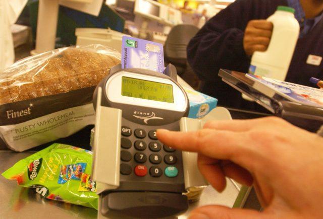 A shopper pays using a debit card (Fiona Hanson/PA)