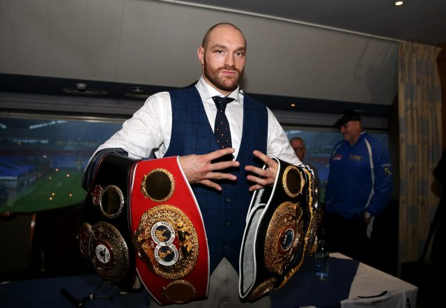 Tyson Fury poses with his belts