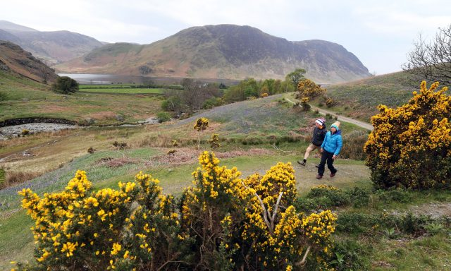 People go for a walk through Rannerdale in the Lake District (Owen Humphreys/PA)